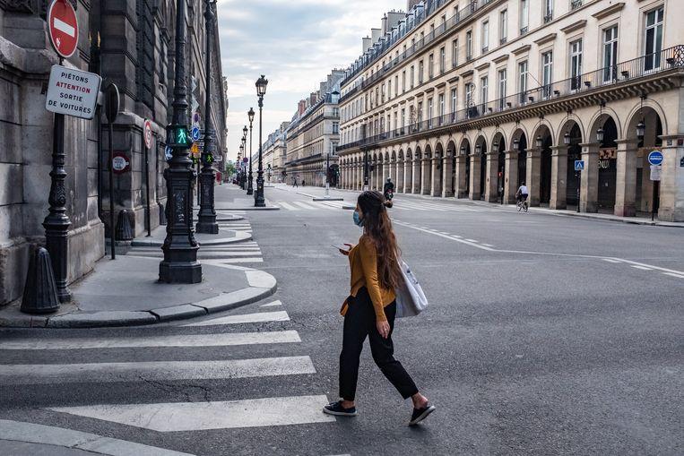 Een vrouw loopt door verlaten straten in Parijs. Frankrijk gaat vanaf 11 mei langzaam de lockdown afbouwen. Beeld Joris Van Gennip