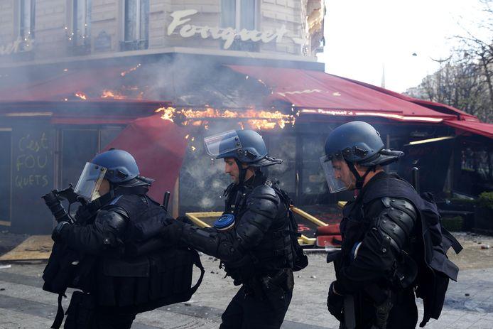 Oproerpolitie stelt zich op voor de brandende pui van het beroemde Parijse restaurant.