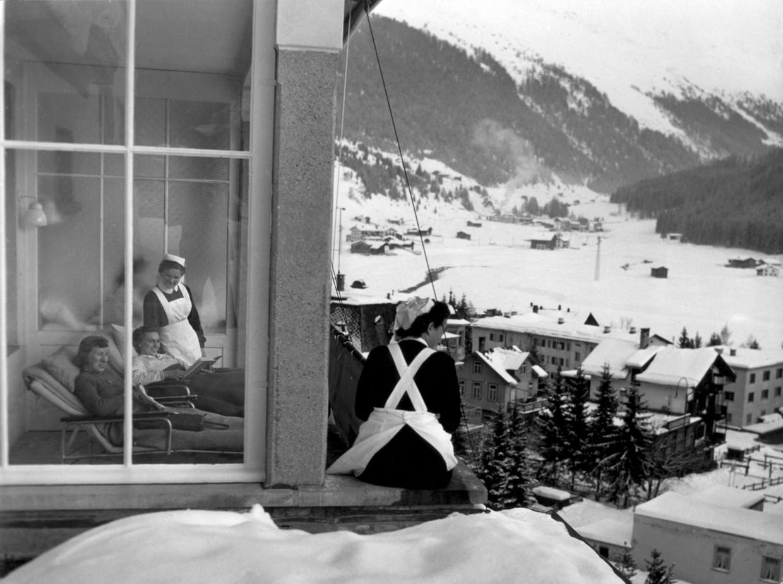 Tuberculose-patiënten en hun verpleegsters genieten van de frisse lucht en het uitzicht in het sanatorium in Davos, in 1950. Beeld Henk Blansjaar/ Spaarnestad