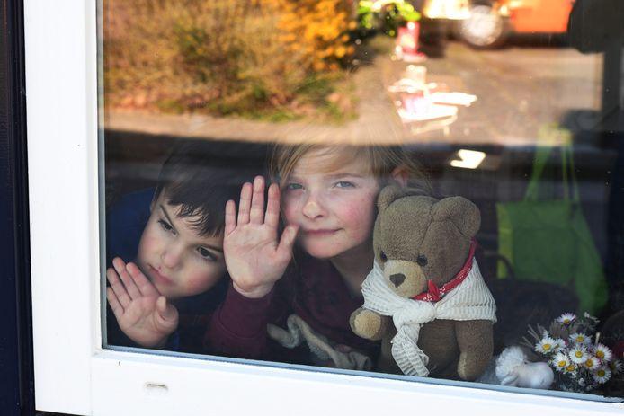 Amber en Ivar van Dommele voor het raam met hun beer.