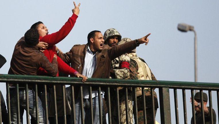 Mubarak-aanhangers schreeuwen naar de betogers vanaf een brug in de buurt van het Tahrirplein in Caïro. Militairen proberen hen te kalmeren. Beeld reuters