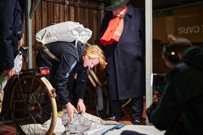 Sheltersuit-oprichter Bas Timmer legt de sheltersuit aan de dakloze Gerard