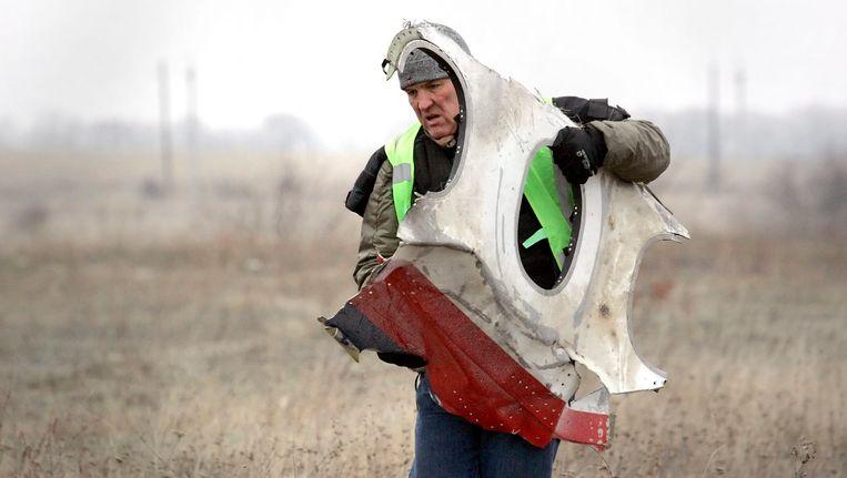 Een arbeider bergt een deel klein onderdeel van het toestel van Malaysia Airlines Beeld epa