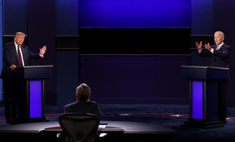 De Amerikaanse president Donald Trump (links) en zijn uitdager Joe Biden (rechts) tegenover elkaar tijdens het debat in Cleveland, waar Fox News-presentator Chris Wallace (midden) grote moeite heeft de orde te bewaren.   Beeld Jonathan Ernst / Reuters