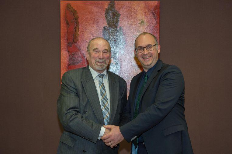 Oud-burgemeester Erik Jacobs (N-VA, links) schudt de hand van huidig burgemeester Bart Seldeslachts (N-VA.).