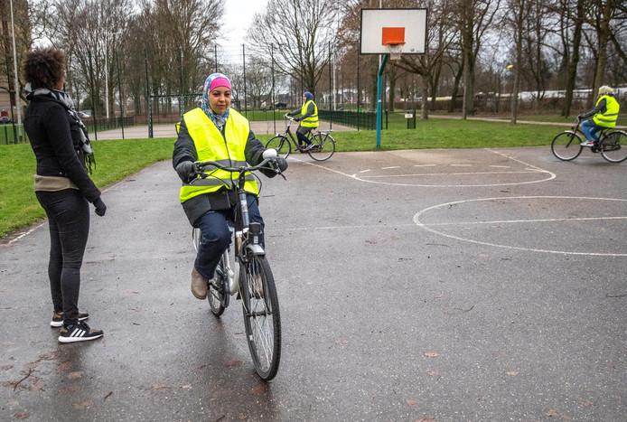 Een vrijwilligster helpt de dames bij de fietslessen.