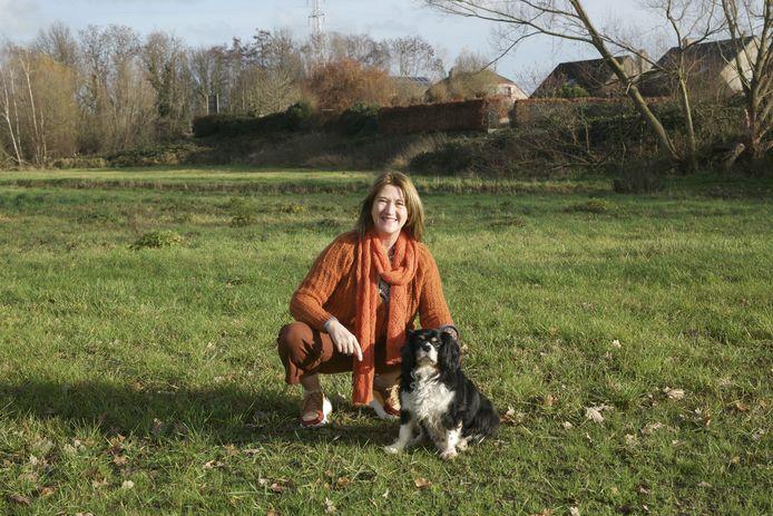 Schepen van Audenhove met haar eigen hond op het grasperk waar straks een heuse hondenweide komt.