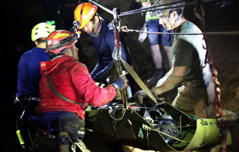 Reddingswerkers zijn bezig met een zojuist gered voetballertje dat op een brancard ligt.