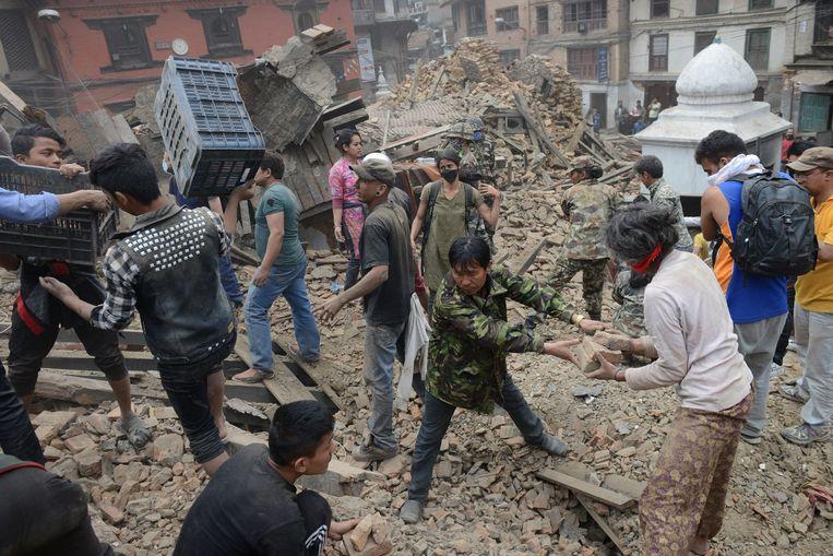 Mensen zijn begonnen met het ruimen van puin op het Koningsplein (Durbar Square) in het centrum van Kathmandu. Beeld anp
