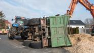 VIDEO. Tractor met aanhangwagen vol verhakseld hout kantelt op rotonde