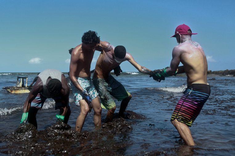 Vrijwilligers zitten onder de olie terwijl ze die proberen te verwijderen uit de zee bij Cabo de Santo Agostinho in de staat Pernambuco. Beeld AFP
