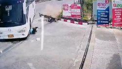 Passagier motorfiets schuift onder bus, maar is als bij wonder ongedeerd