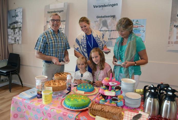 Anna (8) met zusje Julia en moeder Annemarie. Links en rechts gemeenteleden van de Pelgrimskerk, die een taartje voor het goede doel eten.
