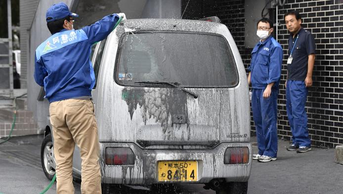 Een man spoelt vulkanische as van zijn auto.
