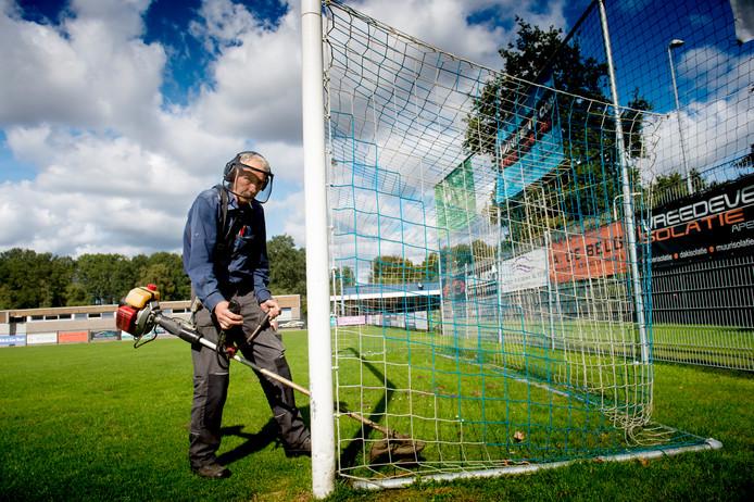 Henk Sangers in actie op Sportpark Nagelpoel. Samen met Manus Bartels en Jan van den Hoogen zorgt hij voor een groene grasmat.