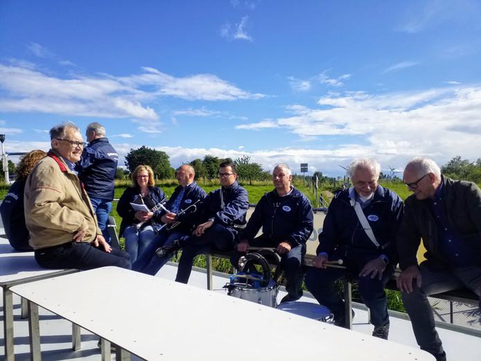 Leden van muziekvereniging Determinato uit Klundert genieten van de overtocht op het dak van de Waterpoort-rondvaartboot.