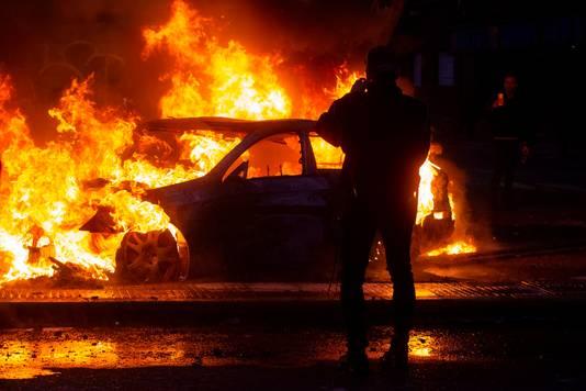 Een auto gaat in vlammen op tijdens de onlusten in de Chileense hoofdstad Santiago.