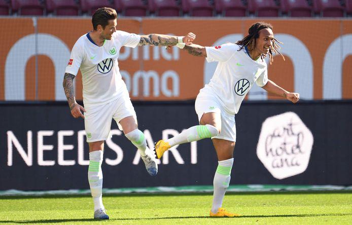 Daniel Ginczek en Kevin Mbabu vieren coronaproof de goal van Wolfsburg.