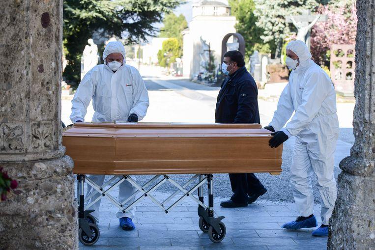 Begrafenisondernemers in beschermende kleding verplaatsen een kist bij een begraafplaats in Bergamo.  Beeld AFP
