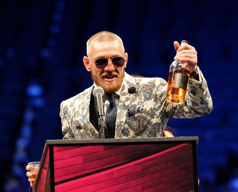 Conor McGregor op een persconferentie na de Money Fight met een fles 'Notorious Whiskey'.