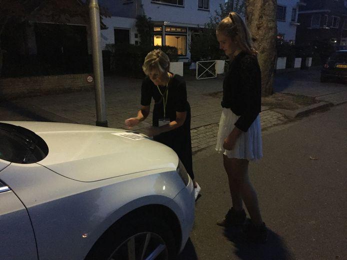 Bianca en Nathalie zoeken de auto's bij de kentekens, één van de opdrachten tijdens het buurtfeest