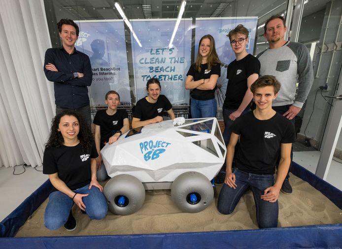 De initiatiefnemers Edwin Bos en Martijn Lukaart samen met het Minor Robotics team van de TU Delft en de proof of principle van DE strandafvalrobot .