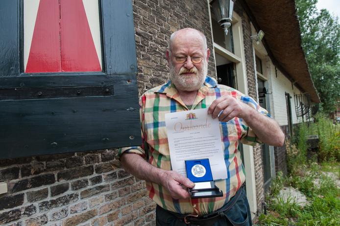 Gouda, Bij zijn historische woning aan de Bloemendaalseweg toont Ton van Duin de vrijwilligerspenning van de stad Gouda die hij heeft ontvangen voor zijn jarenlange inzet voor behoud van Kaasmarkt,.
