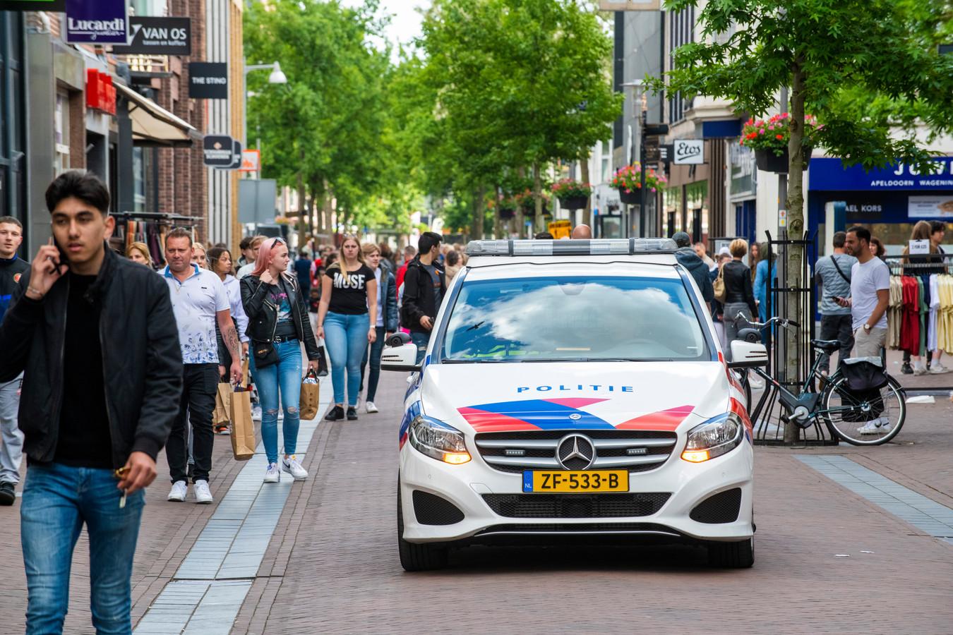 ,,Ga naar huis!'' Vanuit een politiewagen krijgen bezoekers van de Apeldoornse binnenstad te horen dat ze moeten vertrekken omdat het te druk is.