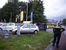 Auto kantelt bij botsing, hek van autobedrijf omvergereden