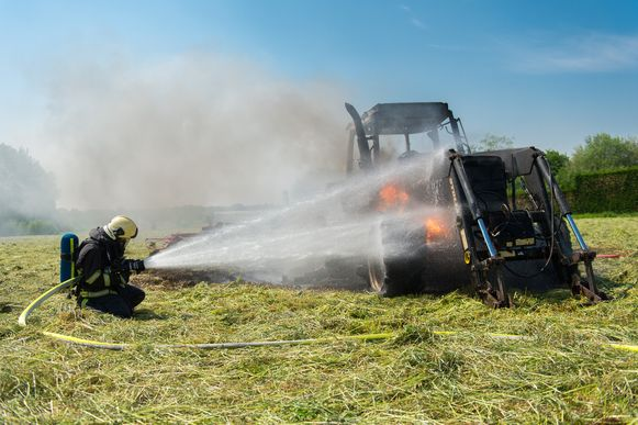 Een brandweerman probeert de vuurhaard aan de tractor onder controle te krijgen.