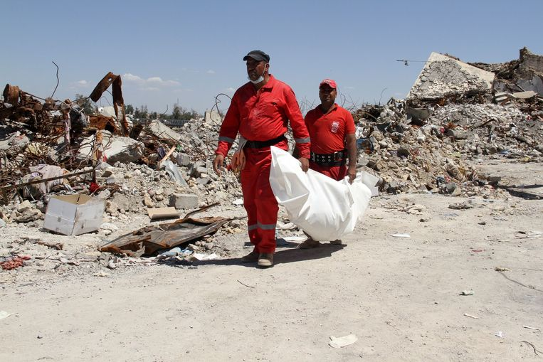 Leden van het bergingsteam van de Iraakse Burgerbeveiliging bergen een lijk, gevonden in de puinhopen van Mosul. Beeld AFP