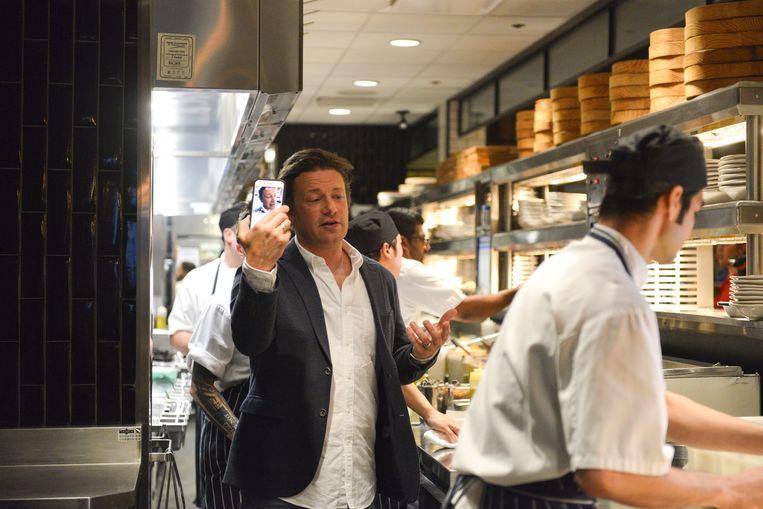 """Jamie Oliver, terwijl hij zichzelf filmt in één van zijn 43 restaurants. """"Ik was heel goed in het runnen van één zaak"""", geeft hij nu toe."""