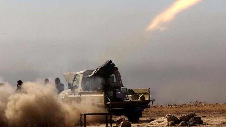 Koerdische Peshmerga's vuren een raket af vanaf een berg vlakbij Mosul. Beeld AFP