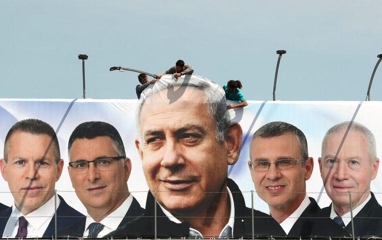 Een verkiezingsfoto van de minister-president van Israël, Benjamin Netanyahu (midden), en zijn partijkandidaten, wordt opgehangen in Jeruzalem. Beeld REUTERS
