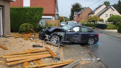 Automobilist ramt houten omheining na botsing