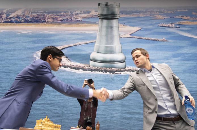 Anish Giri (links) begroet Magnus Carlsen (rechts).