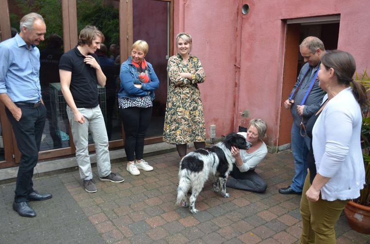 Deze bezoekers maken kennis met een hond in de tuin van het café.