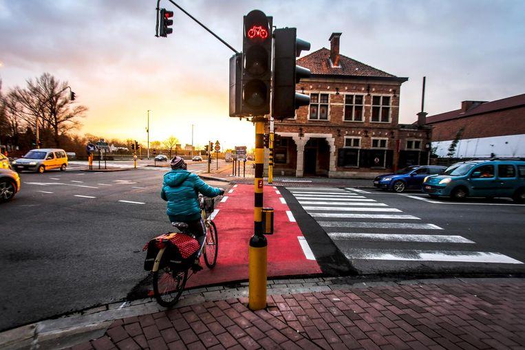 Een fietsster wacht net naast het verkeerslicht totdat ze op het fietspad mag oversteken.