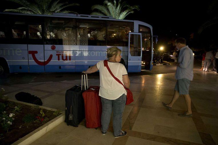 Toeristen wachten op een bus om het Imperial hotel te verlaten Beeld afp