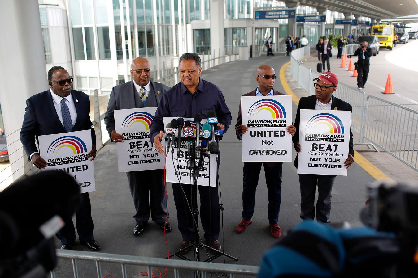 De Amerikaanse dominee Jesse Jackson (midden) protesteert op het vliegveld O'Hare in Chicago, tegen de hardhandige behandeling van passagiers.