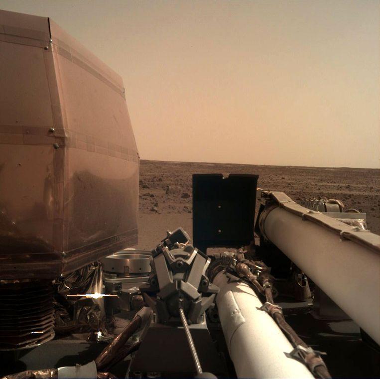 """De Amerikaanse ruimtevaartorganisatie NASA heeft een eerste haarscherpe foto gedeeld die de InSight nam na zijn landing op Mars. """"Er is hier een stille schoonheid"""", tweette NASA maandagnacht bij de foto, waarna de Marsverkenner aan zijn missie begon."""
