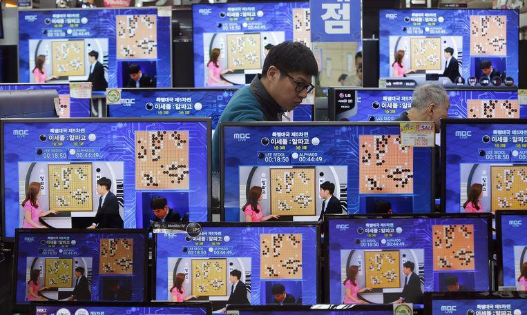 Op schermen in een elektronicazaak in Seoul is de tweekamp te zien tussen Google-computer AlphaGo en de Zuid-Koreaanse wereldkampioen go Lee Sedol. De tweekamp eindigde in 2016 in een 4-1 overwinning voor AlphaGo. Beeld AP