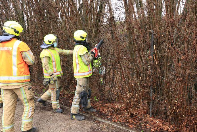 De brandweer moest een omheining doorknippen om tot aan het wrak te geraken.