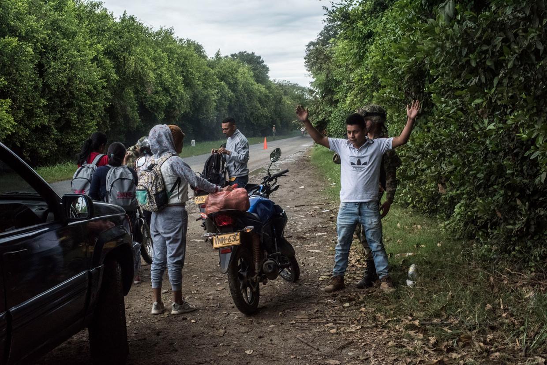 Soldaten van het Colombiaanse leger controleren reizigers op drugs en wapens op een snelweg in de buurt van  Corinto.