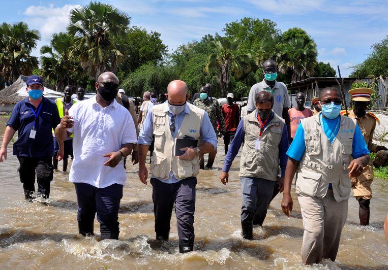 Alain Noudehou en Matthew Hollingworth van het WFP waden in september door het door overstromingen geteisterde Jonglei State in Zuid-Sudan. Beeld REUTERS