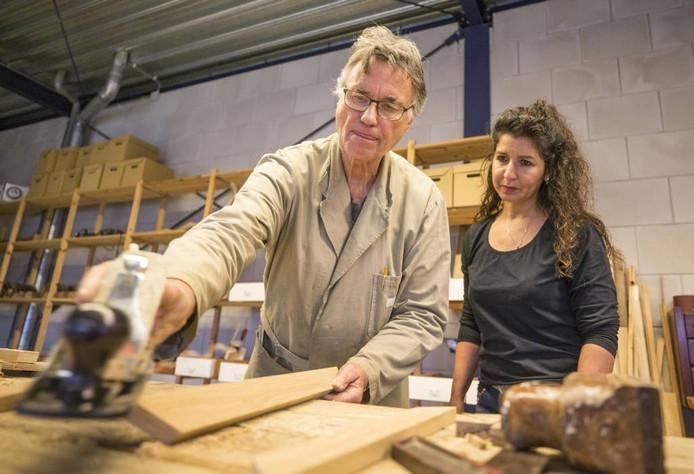 Marinus Vreeke (links) laat Ouafaâ Verzijden zien hoe hij met een schaaf het hout voor een lijst afwerkt.