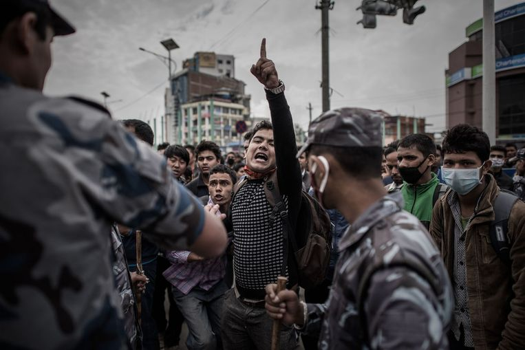 Hopeloze inwoners van Kathmandu schreeuwen naar de Nepalese oproerpolitie. Ze vinden dat de hulpverlening te langzaam op gang komt. Beeld afp