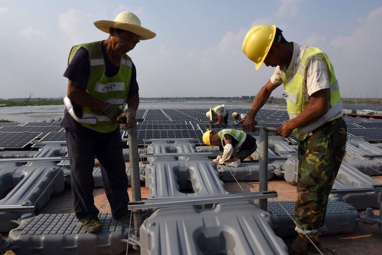 Onderhoud aan het waterzonnepark in China. Beeld AFP