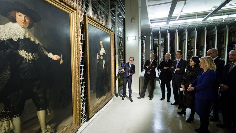 Delegaties van Nederland en Frankrijk in Parijs bij de twee portretten. Beeld anp