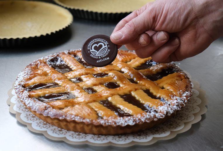 Het logo van de VLAM in chocolade als afwerking op de taart.